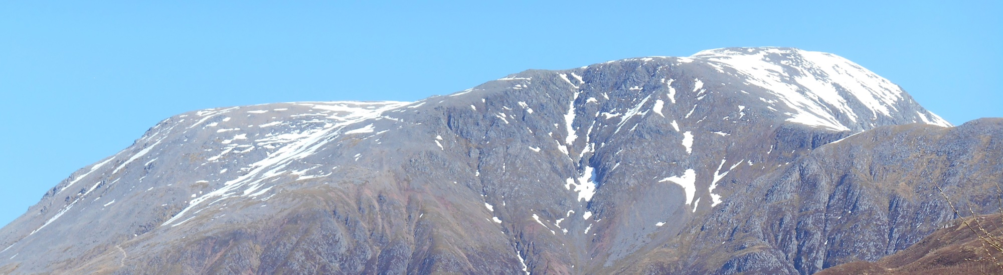 Summit of Ben Nevis with a dusting of snow and clear blue sky.