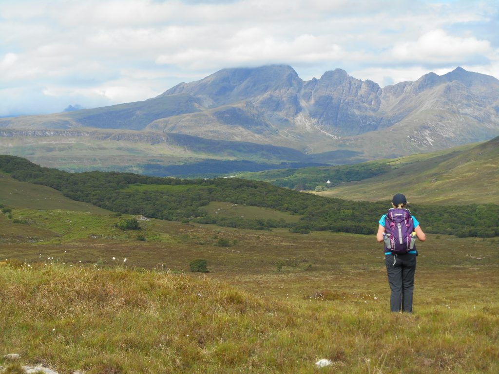Lady walking on The Skye Trail with The Cuillin hills in the background.