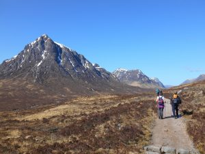 Walking past Buachaille Etive Mòr on The West Highland Way with bright blue sky