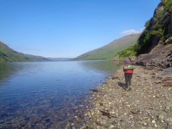 Walking along the shore of a loch on The North West Wilderness Weekend