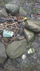 The remains of a fire and rubbish on the shore of Loch Lomond on the The West Highland Way