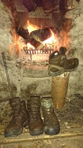 Drying walking boots by an open fire in a bothy