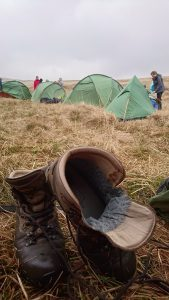 Airing a pair of walking boots with green tents in the background.